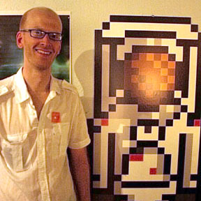 Zachary and a giant cut-out of the pixel zachstronaut logo.